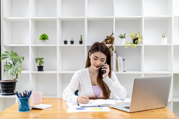 Bella donna d'affari asiatica seduta nella sua stanza, che parla con il suo partner tramite telefono cellulare e controlla i documenti finanziari, è una dirigente donna di una startup. gestione finanziaria.