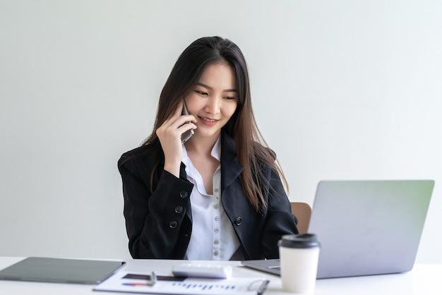 Bella donna d'affari asiatica seduta a parlare al telefono con un computer portatile e documenti alla scrivania dell'ufficio.