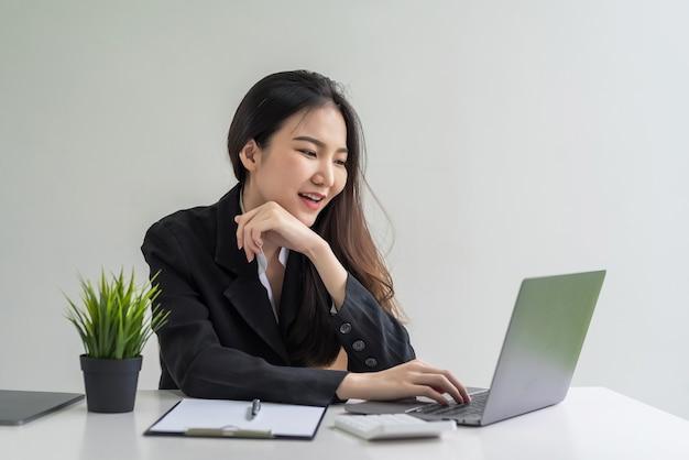 Bella donna di affari asiatica che lavora con il computer portatile in ufficio.