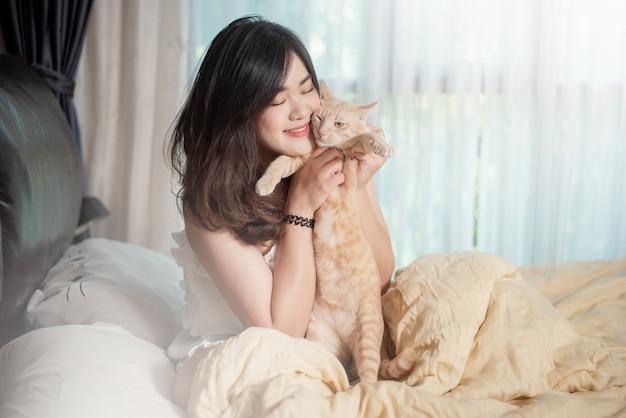 La bella donna asiatica dell'amante del gatto sta giocando con il gatto nella sua stanza