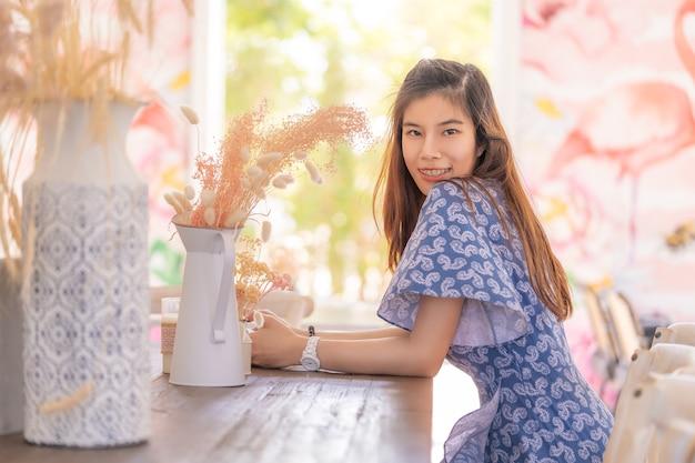 Bella signora di sguardo cinese asiatica che si siede ad una barra di legno