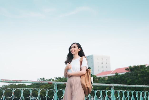 La bellissima studentessa universitaria asiatica che tiene in mano i suoi libri si alza e si veste con abiti di moda di strada in uno spazio pubblico all'aperto con sfondo di edificio moderno