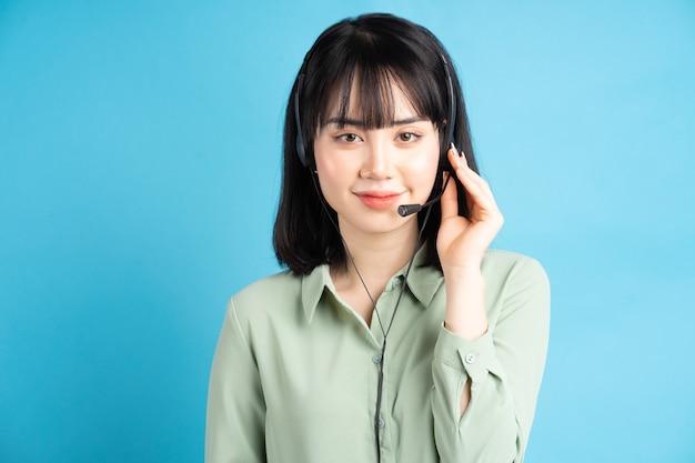 Il bello lavoratore femminile asiatico di assistenza al cliente sta portando le cuffie