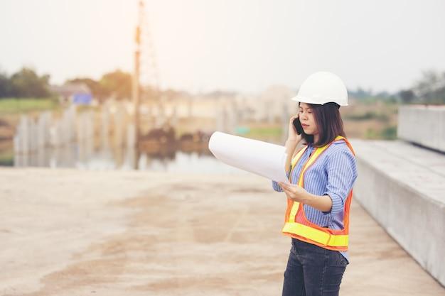 Bello ingegnere femminile asiatico in elmetto di sicurezza bianco che fa lavoro al cantiere fuori ufficio. idea per strada autostradale moderna donna lavoratrice