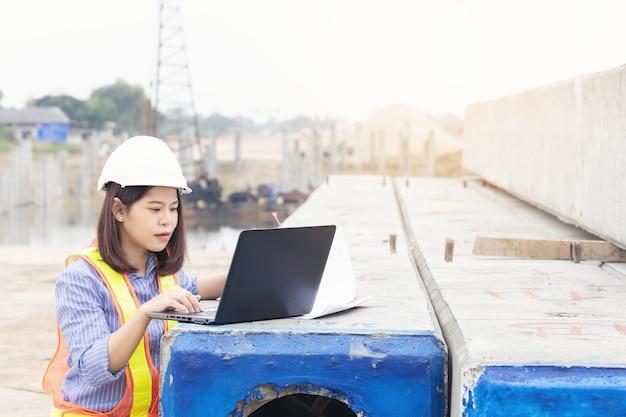 Bello ingegnere femminile asiatico in elmetto di sicurezza bianco utilizzando notebook computer portatile facendo lavoro in cantiere al di fuori dell'ufficio. idea per la donna lavoratrice moderna.