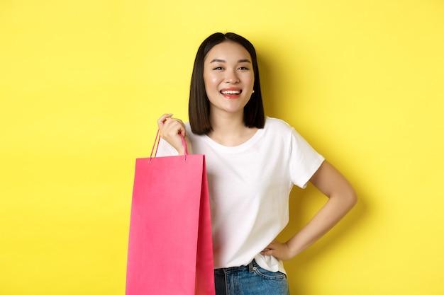Bello modello femminile asiatico in maglietta bianca, tenendo la borsa della spesa e sorridendo soddisfatto, in piedi su sfondo giallo.