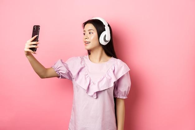 Bella ragazza asiatica blogger prendendo selfie in cuffie wireless, fare foto per i social media su smartphone, in piedi in abito su sfondo rosa.