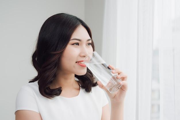 Bella ragazza asiatica che beve un bicchiere d'acqua.
