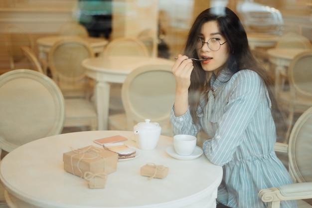 Bella ragazza asiatica che gode di un tè caldo in caffè mentre aspettando qualcuno e avendo scatola attuale su una tavola, vista attraverso il vetro di finestra