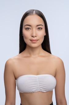 Bella ragazza asiatica che mantiene il sorriso sul viso, in piedi isolata su bianco