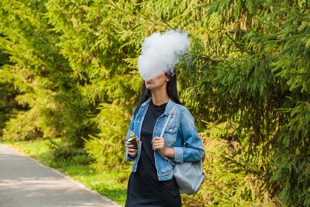 Bella ragazza asiatica fuma in un luogo pubblico.