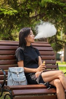Una bella ragazza asiatica fuma uno svapo in un luogo pubblico. il danno del fumo