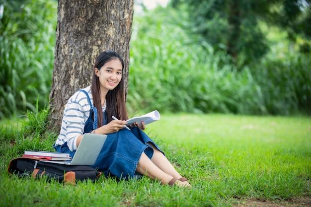I bei libri asiatici della tenuta della studentessa e sorridere e l'apprendimento e il concetto di istruzione sul parco di estate per si rilassano il tempo