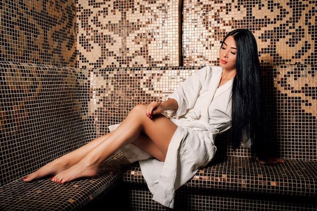 Bella ragazza asiatica in un asciugamano con lunghi capelli neri e gambe lunghe in un hammam turco
