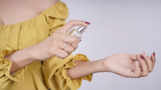 Bella ragazza asiatica che prova profumo sulla sua mano isolata su fondo bianco