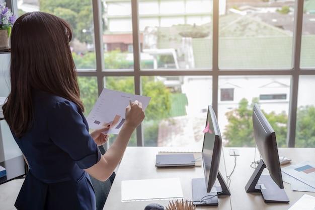 Una bella ragazza asiatica che indossa un abito blu scuro, in piedi in ufficio in un ufficio moderno e guardando i documenti e la parte anteriore è una grande finestra di vetro.