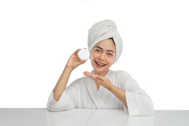 Bella ragazza asiatica con l'asciugamano sulla testa che tiene la bottiglia di vaso di crema con gesto della mano presente