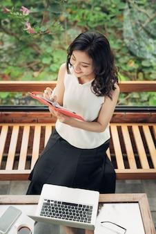 Bella ragazza asiatica che scrive note in una scrivania a casa