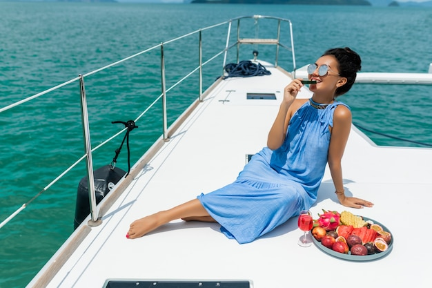 Una bella signora asiatica in un vestito blu su uno yacht beve champagne e mangia frutta