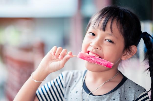 La bella bambina asiatica mangia il gelato di estate a casa