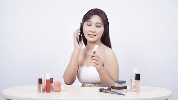 Bella discussione di trucco asiatico al telefono isolato su sfondo bianco