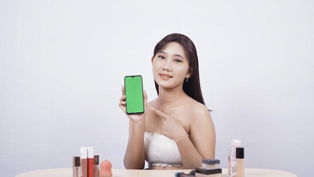 Bellissimo trucco asiatico che mostra il gesto ok dello schermo dello smartphone isolato su sfondo bianco