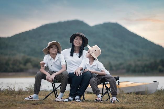 Bella madre asiatica e figlio che fanno picnic e nella festa estiva di pasqua su un prato vicino al lago e alla montagna