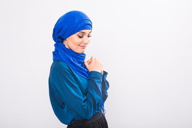 Modello di bella donna musulmana asiatica in posa su sfondo bianco in studio.