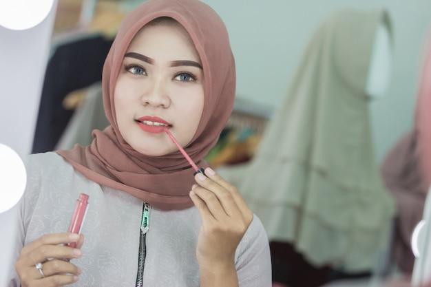 Bella donna musulmana asiatica con hijab che applica rossetto