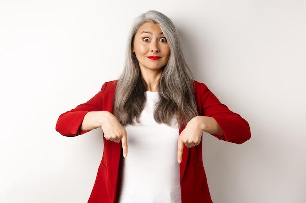 Bella donna asiatica senior in elegante giacca sportiva rossa, puntando le dita verso il basso e sorridendo eccitata, mostrando pubblicità, sfondo bianco.