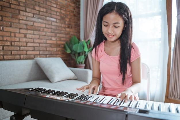 Bella ragazza teenager asiatica che gioca uno strumento di pianoforte