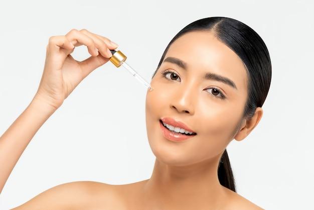 Bella donna asiatica che applica siero idratante anti invecchiamento sul suo viso per i concetti di cura della pelle e di bellezza