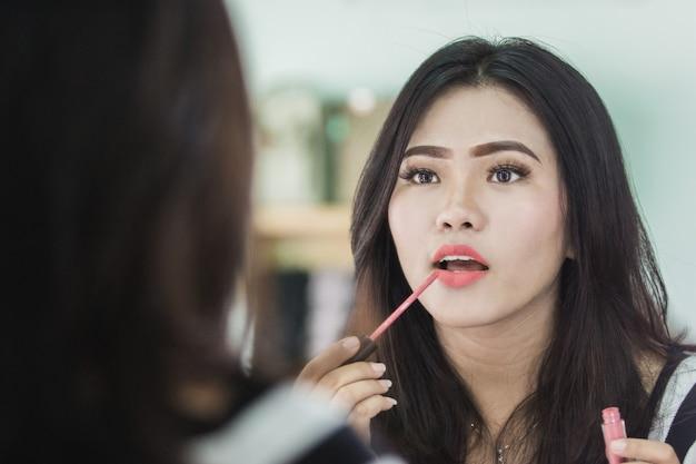 Bella donna asiatica che applica rossetto