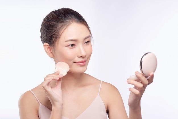 Bella donna asiatica che applica il piumino da cipria al trucco della guancia del cosmetico, bellezza della ragazza con un sorriso sul viso