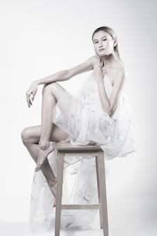 Bella donna asiatica capelli color bronzo che tengono tessuto trasparente e si siedono su uno sgabello per mostrare che la pelle della schiena è, illuminazione da studio su sfondo bianco isolato