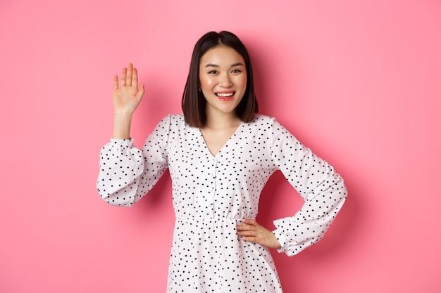 Bella donna asiatica in abito dicendo ciao, agitando la mano per salutare e dire ciao, sorridente amichevole alla macchina fotografica, in piedi su sfondo rosa.