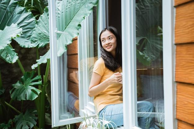 Bella donna asiatica che beve caffè al mattino vicino alla finestra