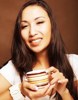 Bella donna asiatica che beve caffè o tè