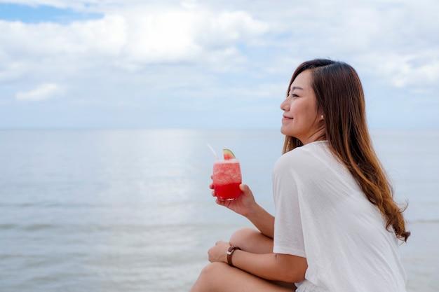Una bella donna asiatica che beve succo di anguria mentre è seduta in riva al mare