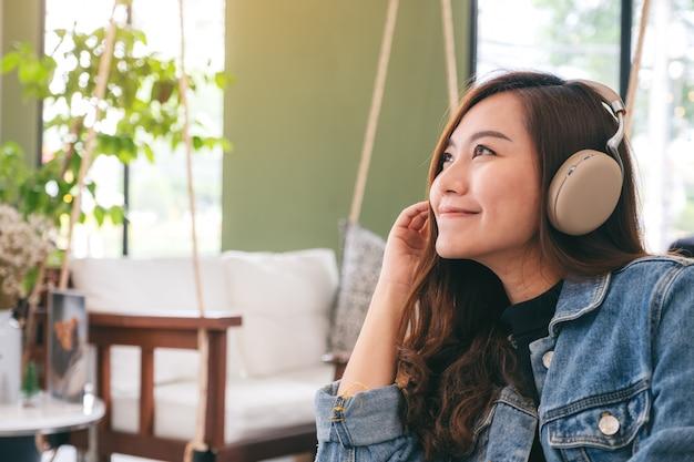 Una bella donna asiatica piace ascoltare la musica con le cuffie con sentirsi felici e rilassati nella caffetteria