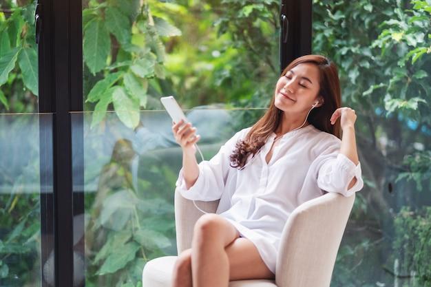 Una bella donna asiatica piace ascoltare la musica con il telefono e l'auricolare a casa, i concetti di natura verde, felicità e relax