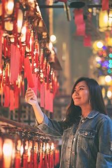 Una bella donna asiatica si è divertita a guardare le lampade rosse e i desideri nel tempio cinese