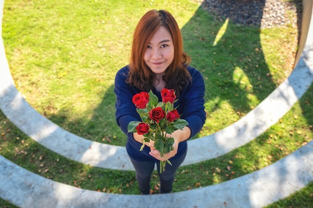 Una bella donna asiatica che dà le rose rosse fiorisce al suo fidanzato il giorno di san valentino con sentirsi felice e amata