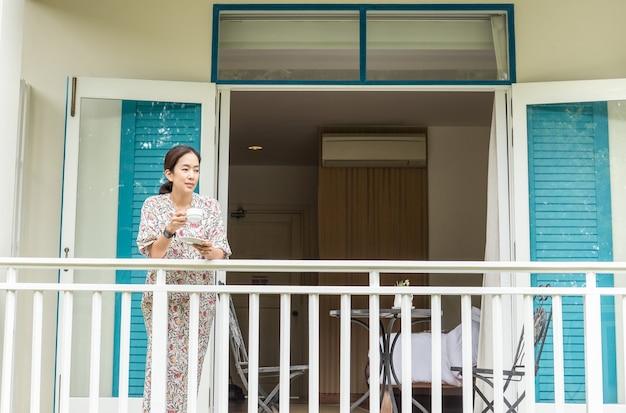 Bella donna asiatica che mangia caffè o tè del mattino al balcone dell'hotel.