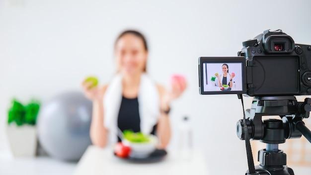 Il blogger in buona salute della bella donna asiatica sta mostrando frutta e cibo dietetico pulito davanti alla telecamera per registrare video vlog in diretta streaming a casa.