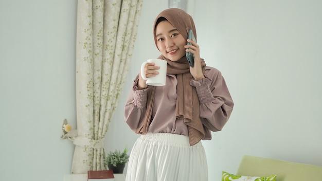 Bella donna asiatica in hijab in piedi che si gode un drink mentre è al telefono a casa