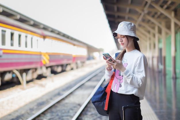 Una bella donna asiatica con in mano una borsa e uno smartphone in cerca di informazioni di viaggio