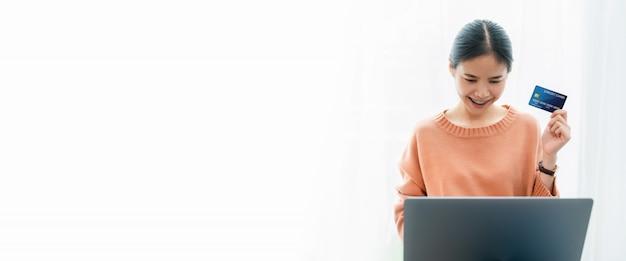 Bella carta di credito asiatica della tenuta della donna e per mezzo del computer portatile digitale che compera online