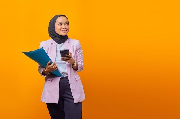 Bella donna asiatica che tiene cartelle e smartphone guardando il lato con una faccia sorridente
