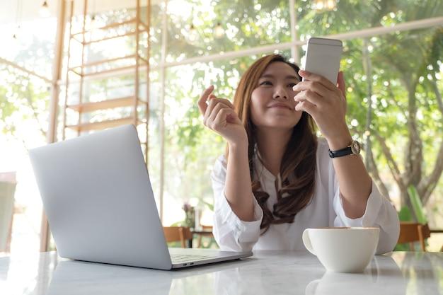 Una bella donna asiatica holding e guardando smart phone durante l'utilizzo di laptop nella caffetteria